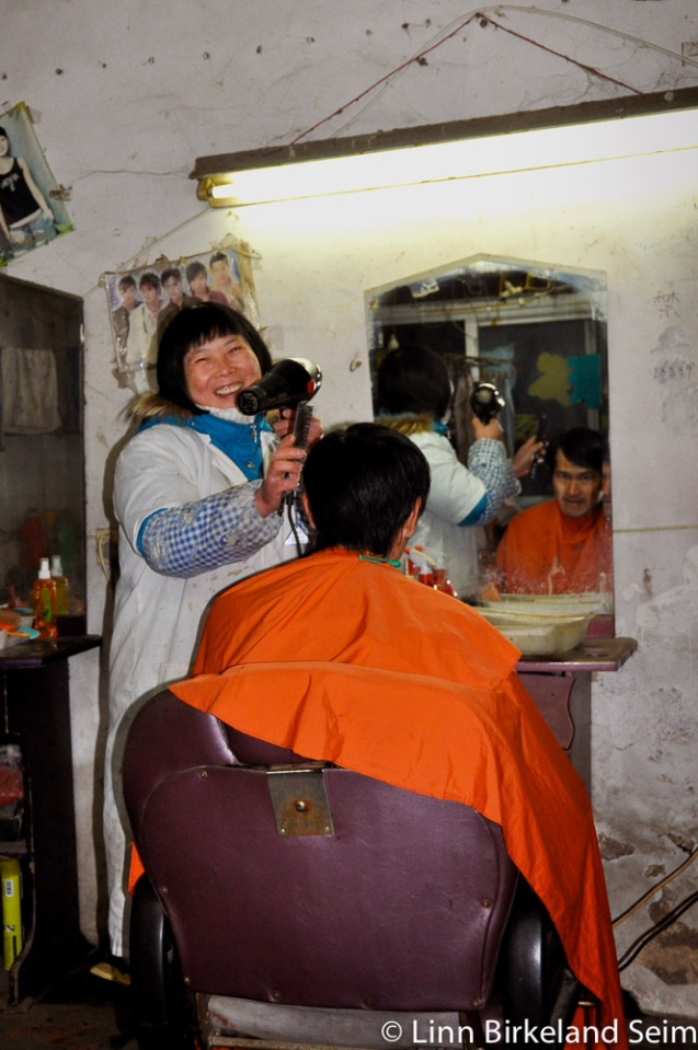 Peeking into a little one-woman business in the back-alleys of Suzhou. China-2010. Hairdresser